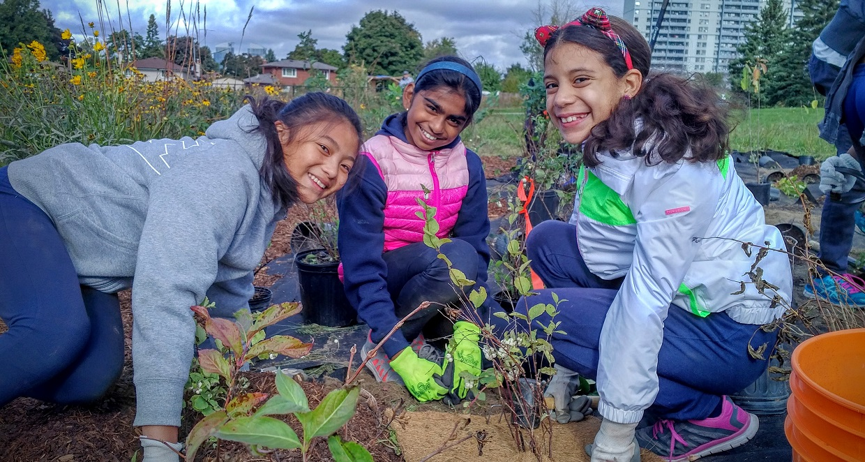 girls planting pollinators in The Meadoway