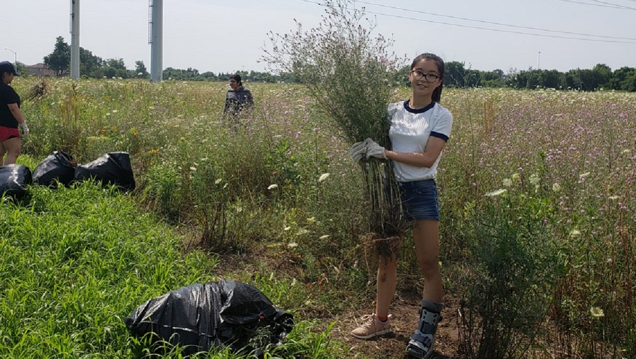 student participates in community planting event in The Meadoway